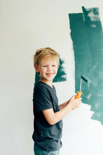 Portrait of smiling boy holding camera over white background