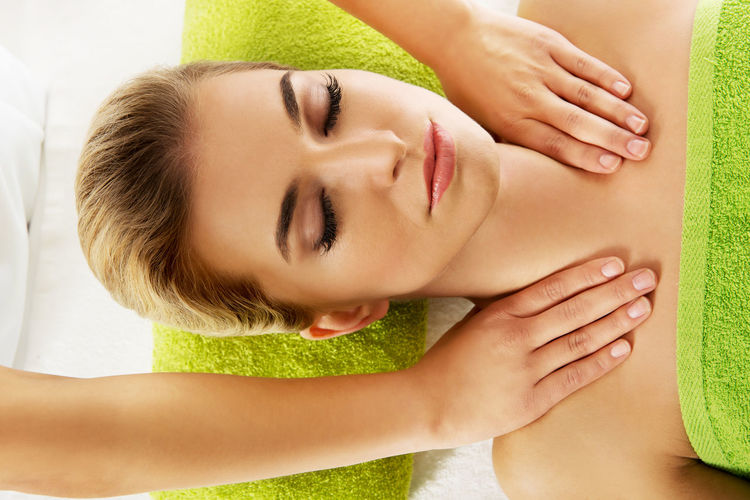 Cropped Hands Of Therapist Massaging Woman Lying On Bed In Spa