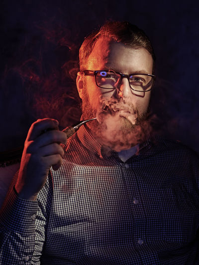Portrait Of Mature Man Smoking While Sitting Against Black Background