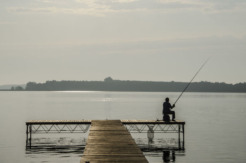 Rear View Of Silhouette Man On Pier Fishing In Sea Against Sky