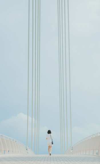 Rear View Of Woman Walking On Bridge Against Sky