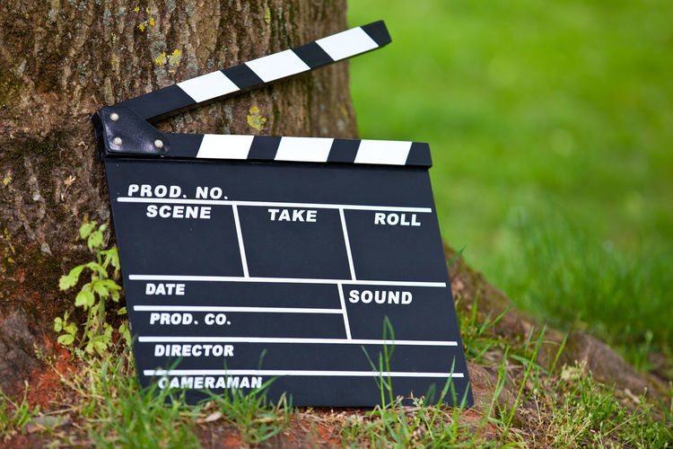 Clapperboard next to tree trunk Clapperboard Director Film Film Production MOVIE Movie Props Outside Text Space Video Video Production