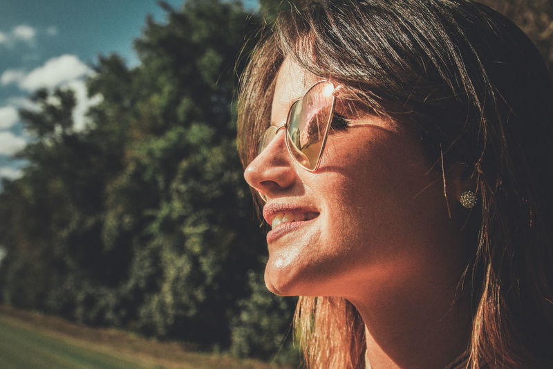 Close-up of smiling young woman wearing sunglasses