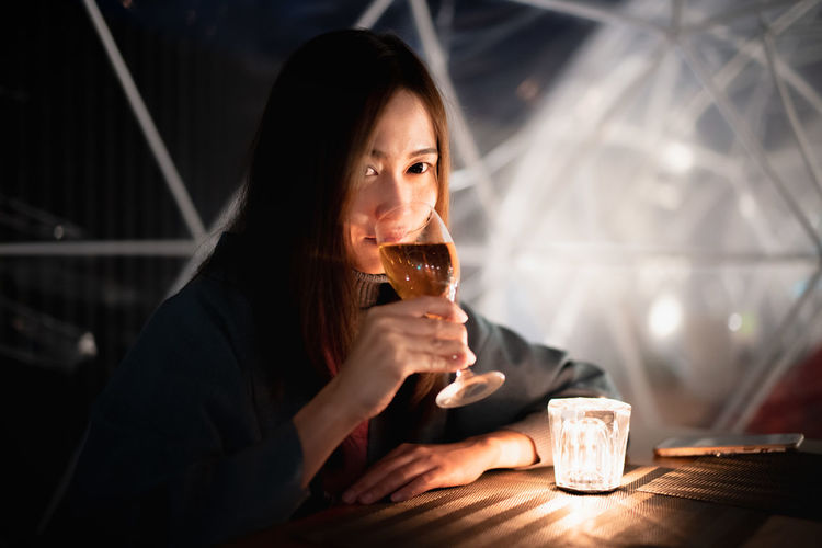 Drink Food And Drink Refreshment Drinking Alcohol Sitting Glass Holding Real People One Person Indoors  Lifestyles Young Adult Leisure Activity Table Portrait Adult Drinking Glass Front View Beautiful Woman Contemplation