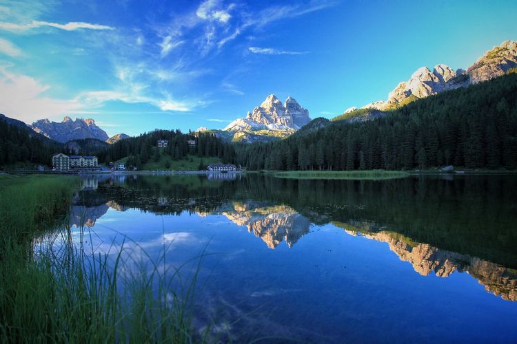 Reflection of rocky mountains in lake against blue sky