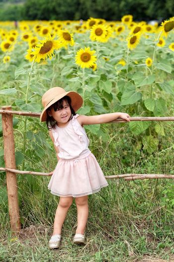 Portrait of girl standing against blooming sunflowers