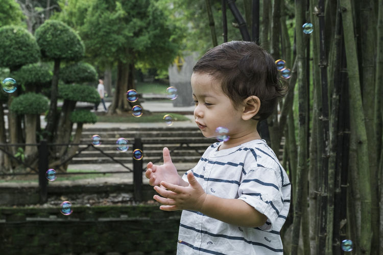 young kid playing with bubble under bright sunny day at public park Child Childhood One Person Side View Plant Males  Boys Real People Standing Casual Clothing Men Holding Focus On Foreground Leisure Activity Lifestyles Day Innocence Tree Bubble Outdoors Hairstyle