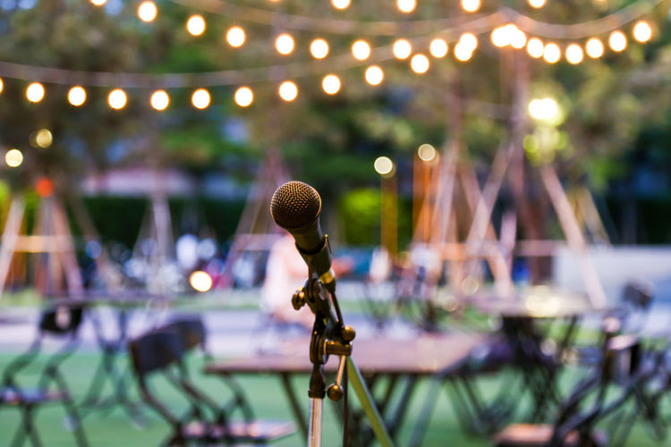 Microphone at party against illuminated light bulbs at dusk
