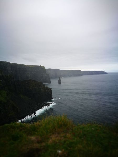 Cliff of Moher Sea Beach No People Nature Coastal Feature Beauty In Nature Cloud - Sky Water Outdoors Scenics Fog Landscape Tranquility Tranquil Scene Vacations Travel Destinations Building Exterior Grass Built Structure Personal Perspective Streetphotography Lost In The Landscape Tranquility Vacations Architecture