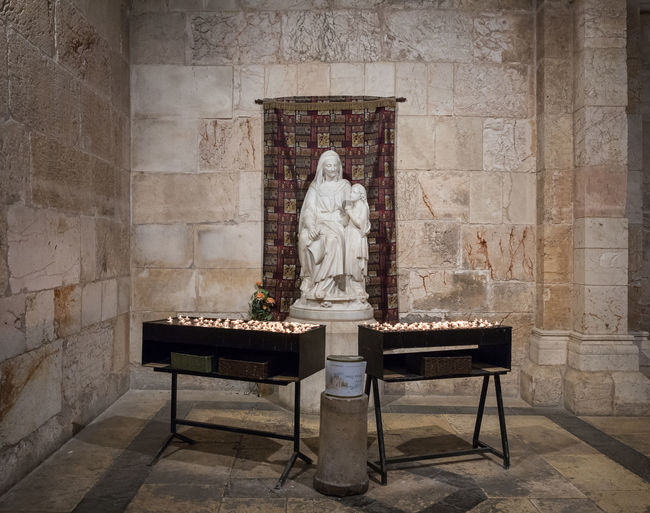 Jerusalem, Israel, March 09, 2019 : Tables with candles stand in front of the statue in the Church of Saint Anne near Pools of Bethesda in the old city of Jerusalem, Israel Tank Roman Cistern Heritage Historic Brick Wall Stone Material Damaged Arch Remains Landmark Ruins Christianity Excavations Scenic View Ancient Archaeological Religion And Beliefs Culture Antique Architecture Jerusalem Israel Old City Church Of Saint Anne And The Pools Of Bethesda Worship