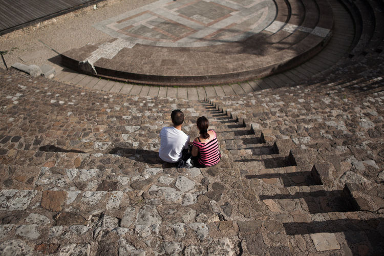 High angle view of couple sitting at amphitheater steps