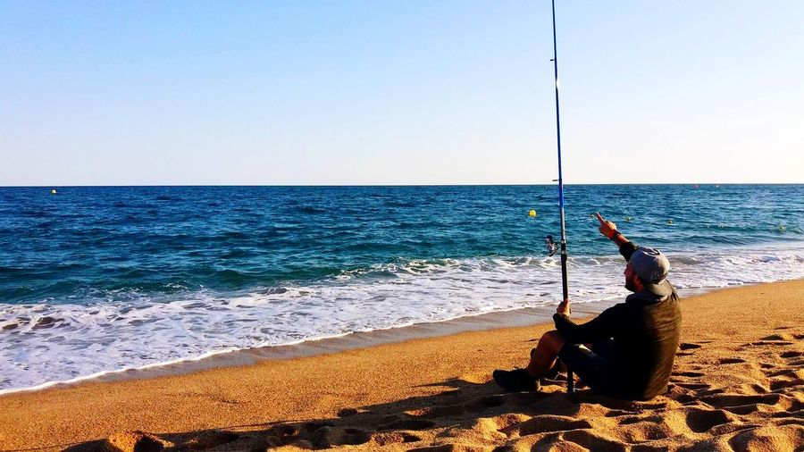 Man with fishing rod sitting at beach against clear sky