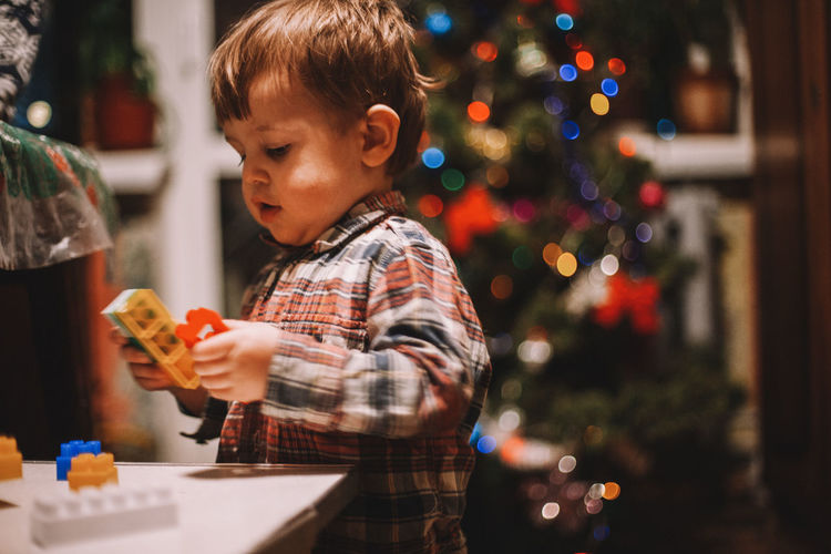 Cute boy holding toys with christmas tree in background