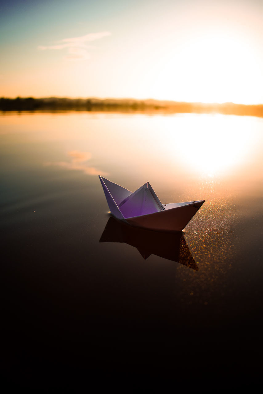 CLOSE-UP OF PAPER FLOATING ON LAKE DURING SUNSET