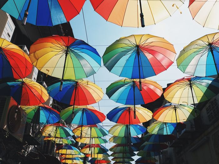 Low angle view of multi colored umbrellas hanging in row