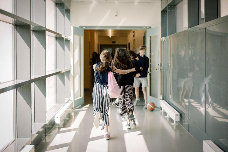 Rear view of two people walking in corridor