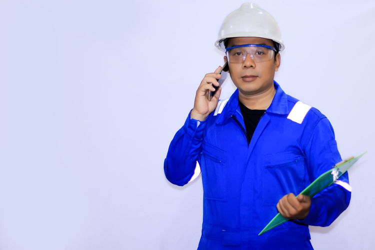 Young Asian engineer Hardhat  Occupational Safety And Health Headwear Warm Clothing Protective Workwear Manual Worker Human Hand Occupation Industry Construction Worker Engineer Manufacturing Occupation Electrician