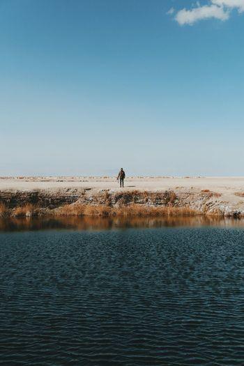 Man standing by river at atacama desert against sky