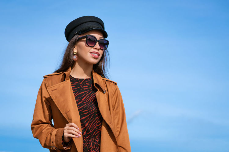 Female portrait of a young woman against a blue sky in sunglasses