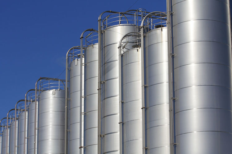 Low angle view of storage tank in factory against sky
