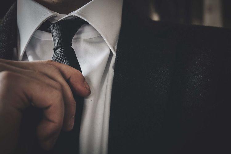 Midsection of man adjusting necktie