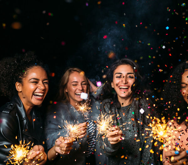 Cheerful female friends with burning sparkler at night