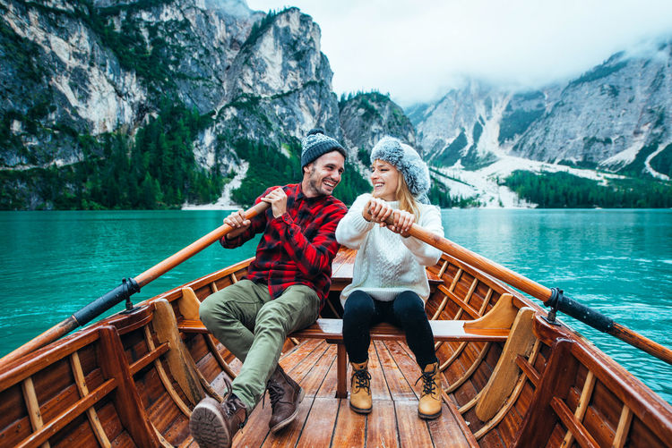 Woman sitting on a boat in lake against mountains