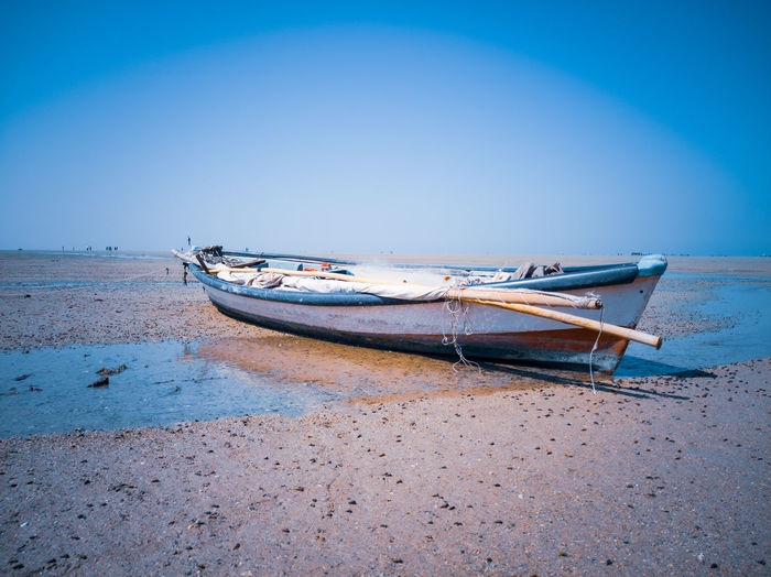Boat moored on beach against clear blue sky