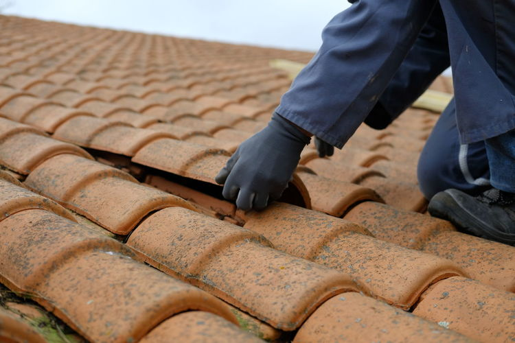 Low section of man repairing roof tiles