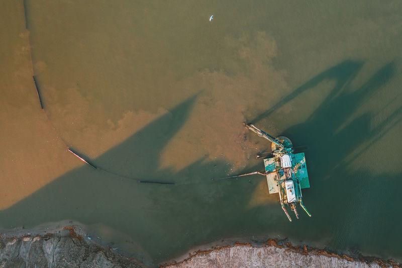 High angle view of abandoned ship on sea against wall