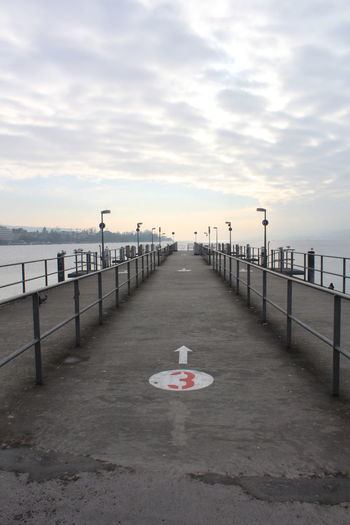 Markings On Pier Over River Against Cloudy Sky