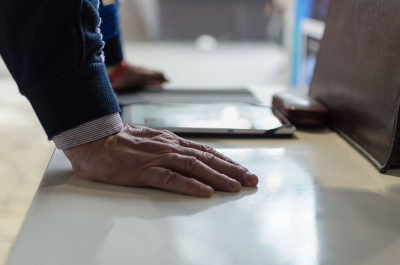 Cropped hands of businessman using digital tablet at desk