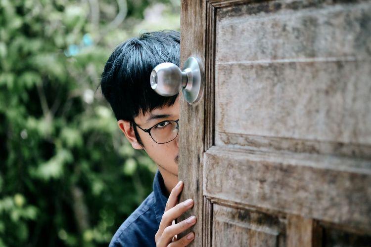 Portrait of man peeking through window