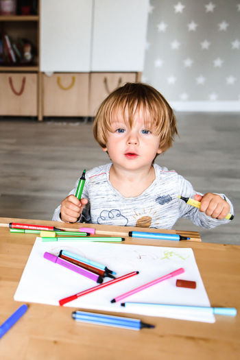 Portrait of boy making face on table at home