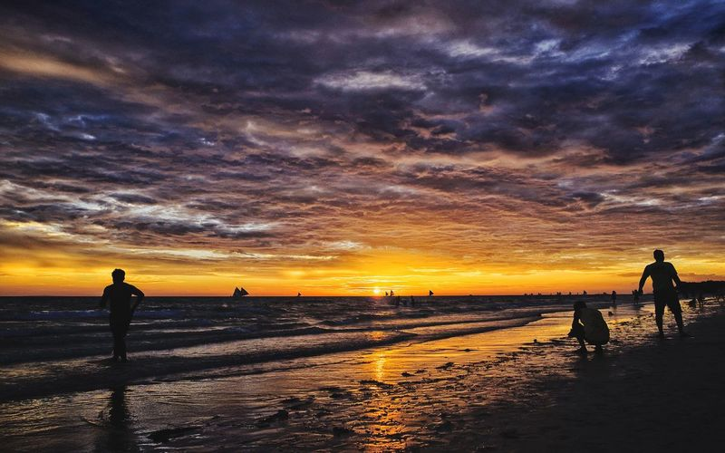 Silhouette of people on beach against cloudy sky