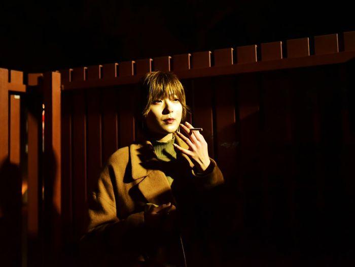 Portrait of boy standing in dark room