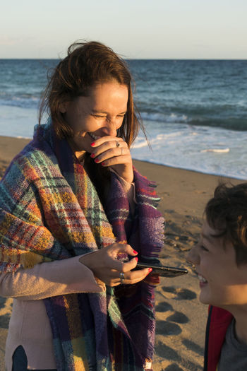 Mother with smart phone and son against sea and sky during sunset