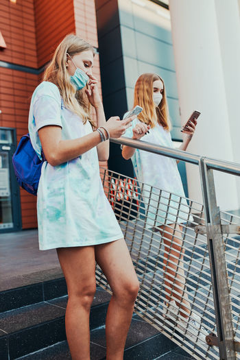 Young women girls spending time together downtown using smartphones social media sending texts
