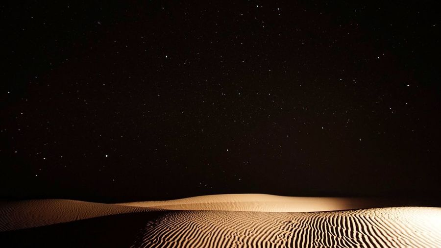 Scenic view of desert against star field at night