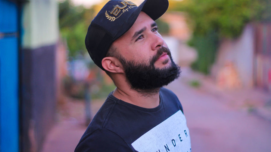 Close-up of thoughtful bearded man wearing cap looking away outdoors