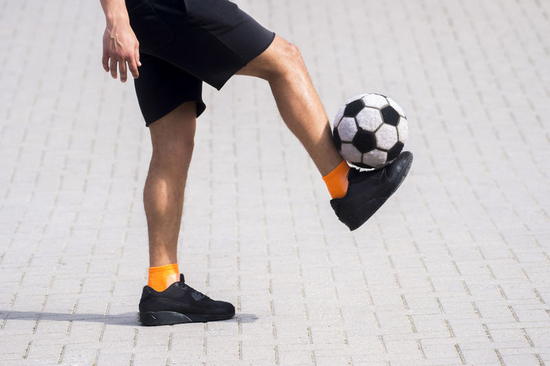 Low Section Of Man Playing Soccer Ball On Footpath During Sunny Day