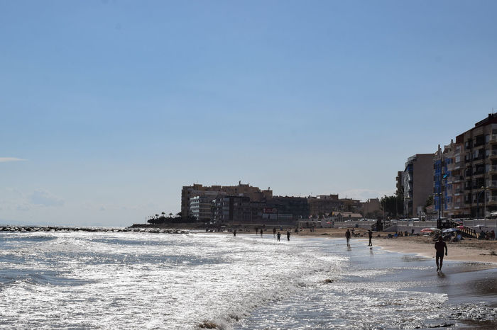 people walking on the beach Sandy Beach Mediterranean  Holidays Vacations Wet Sand City Beach Clear Sky Sand Sky Architecture Shore Office Building Horizon Over Water Ocean Wave Sea Calm Rushing