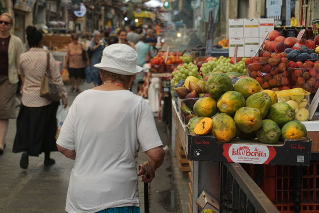 At The Market Market Buy Colour Of Life People People Walking  Festive Season Woman Fat Woman Big Woman Old Woman Woman From The Back People In The Background Fruit Fruits Woman Walking Hat White Hat Snap a Stranger White Shirt at Jerusalem Israel Miles Away Women Around The World