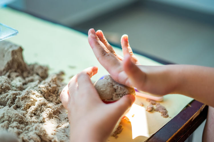 Cropped hand of child playing with sand on table