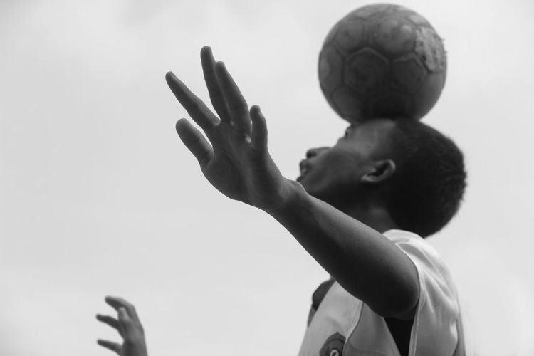 Low Angle View Of Boy Balancing Soccer Ball Against Clear Sky