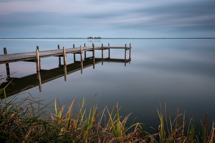 Scenic view of pier on lake against sky