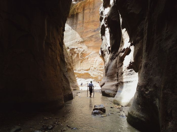 Rear View Of Man Amidst Rocky Mountains At Zion National Park