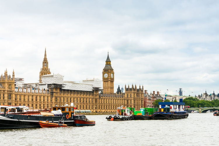 Boats In Thames River By Palace Of Westminster And Big Ben Against Sky