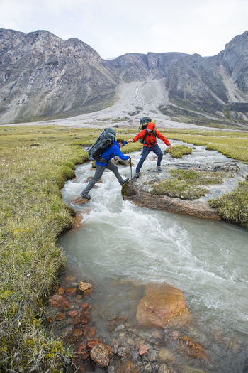 Men surfing on rocks against mountains