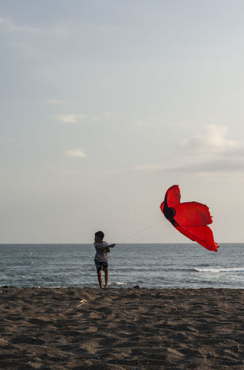 Boy flying kite while standing at beach against sky during sunset